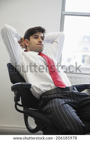 Young Indian businessman contemplating while sitting in office chair - stock photo