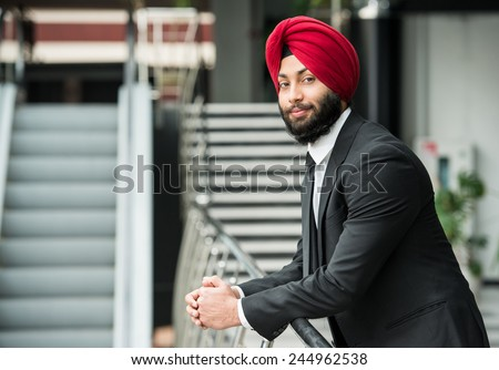 Young indian businessman in modern office is looking at camera. - stock photo