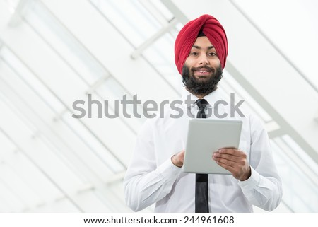 Young indian businessman in modern office with tablet. - stock photo