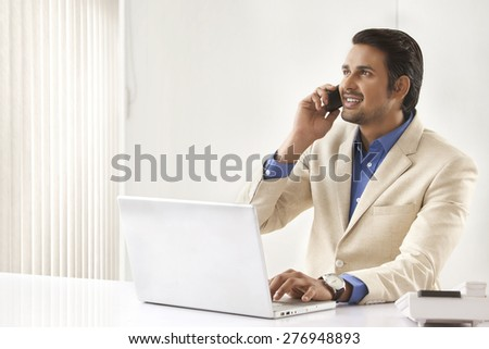 Young Indian businessman on call while using laptop in office