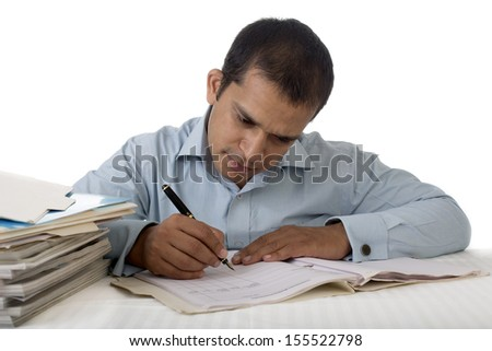 Young Indian Businessman or Office Employee working at his desk amidst a pile of files. Shot on a white background. - stock photo