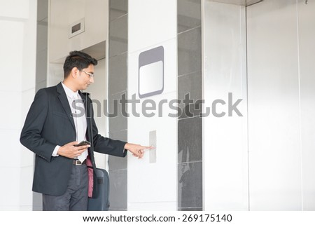 Young Indian businessman pressing on elevator button, waiting door open to enter inside the lift. - stock photo