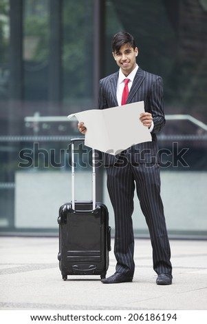 Young Indian businessman with luggage bag reading paper - stock photo