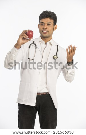 young Indian Doctor with apple on white background.  - stock photo