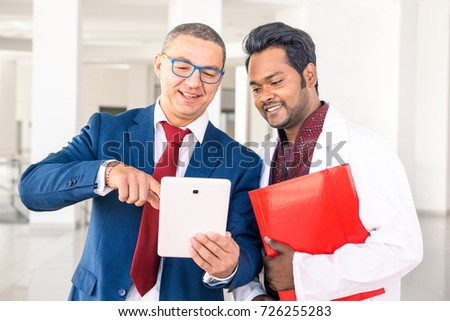 Young Indian doctor with businessman talking in hospital hallway - Salesman holding pad showing health care equipment at asian medical director - Concept of sales, business, deals with multiracial men