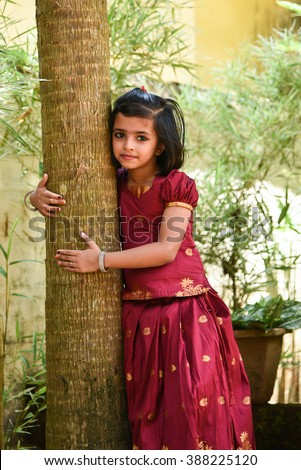 young Indian girl/kids wearing traditional dress for cultural Onam, Vishu Kerala India. Asian child. Beautiful daughter in India sari. Sweet, happy, smiling child in a park hugging a tree. save plants - stock photo
