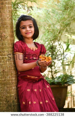 young Indian girl wearing traditional dress for Onam Kerala India . Asian child. Beautiful daughter in traditional India sari. Sweet, happy, smiling child in a park playing with flowers and laughing