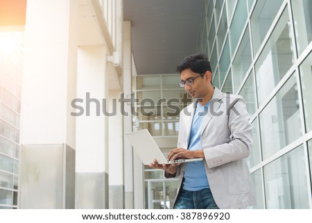 young indian male using laptop outdoor - stock photo