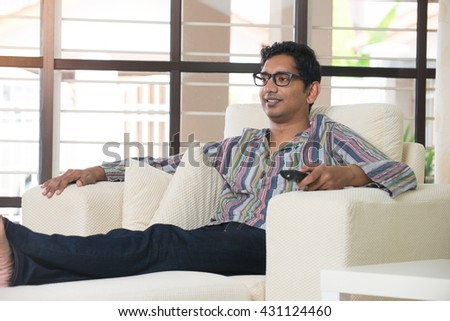 young indian male watching tv - stock photo