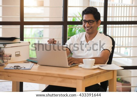 young indian man celebrating success while working - stock photo