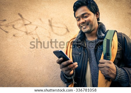 Young indian man holding mobile phone - Cheerful asian model next to old urban wall - Soft vintage filtered look focus on person face                                                              - stock photo