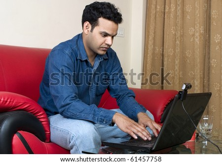 young indian man working at home on  his laptop - stock photo