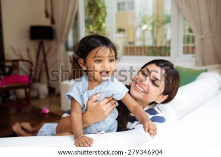 Young Indian mother and her little daughter having fun at home - stock photo