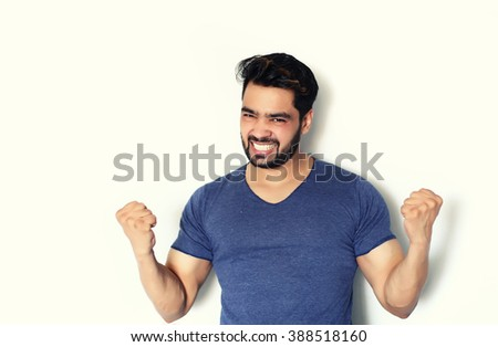 Young Indian Successful man celebrating with arms up - isolated over white - stock photo