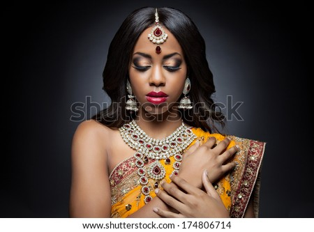 Young Indian woman dressed in traditional clothing with bridal makeup and jewelry - stock photo