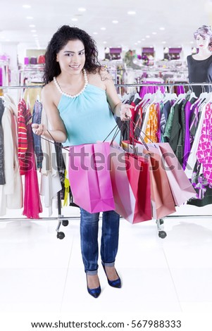 Young Indian woman holding and opening shopping bags while standing in the store