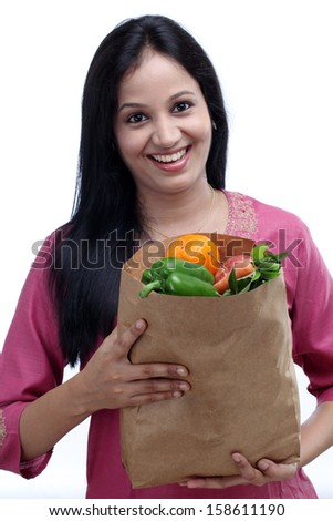Young Indian woman holding grocery bag with full of fruits and vegetables - stock photo