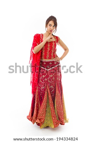 Young Indian woman standing with finger on lips - stock photo