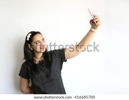 Young Indian woman take selfie of himself against the white background - stock photo