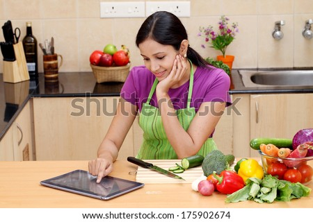 Young Indian woman using a tablet computer in her kitchen  - stock photo