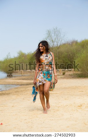 young indian woman walking along the bank of a lake