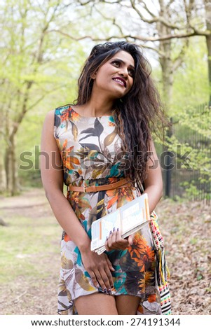 young indian woman walking in the forest with a map - stock photo