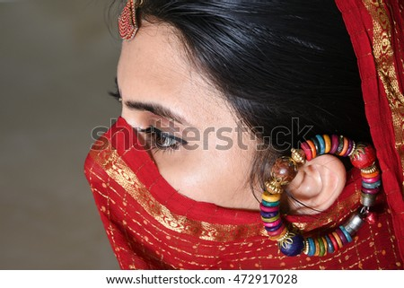 Young Indian woman with beautiful sharp eyes in focus. Rajasthan female with face partially covered with sari/saree. Girl in rural village of India wearing red traditional dress.