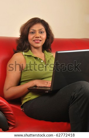 young indian woman with laptop working from home - stock photo
