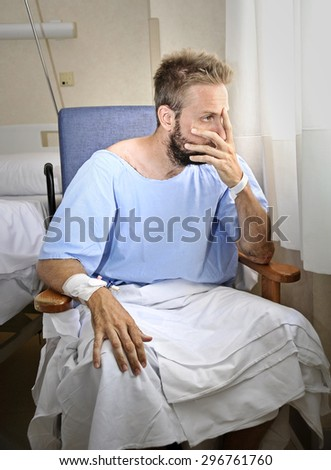 young injured man in hospital room sitting alone in pain looking negative and worried for his bad health condition sitting on chair suffering depression on a sad lonely medical background - stock photo