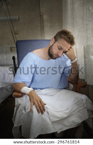 young injured man in hospital room sitting alone in pain looking negative and worried for his bad health condition sitting on chair suffering depression on a sad grunge medical background - stock photo