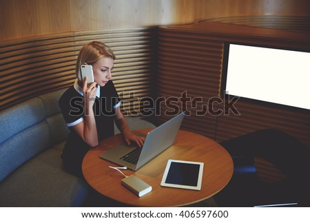 Young intelligent businesswoman is talking on mobile phone with manager her company, while is reviewing the level implementation of work via laptop computer, while is sitting near screen with mock up - stock photo