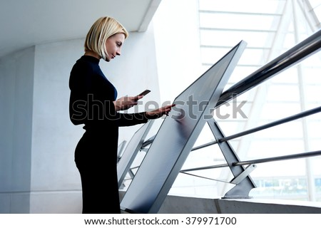 Young intelligent female phoning to partner via mobile phone while selecting information on high tech device, smart businesswoman holding cell telephone while exploring project on interactive monitor  - stock photo