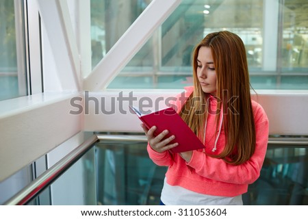 Young intelligent university student holding a notepad reads something at campus indoors, stylish teenager girl with long hair preparing for classes while standing in the hallway of modern college - stock photo