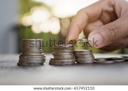 Young intelligent woman hand putting money coin stack growing business on old wooden table with nature background.