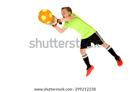Young intense boy soccer goalie blocking shot