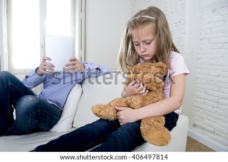 young internet addict father using digital tablet pad ignoring little sad daughter looking bored hugging teddy bear abandoned and disappointed with dad sitting on home couch sofa - stock photo