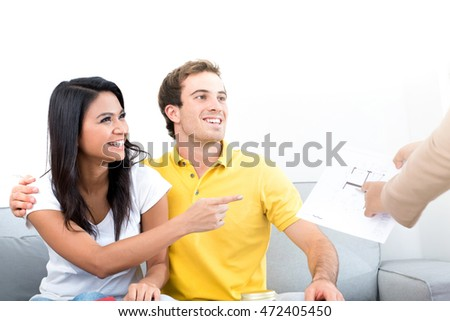 Young interracial couple meeting with  real estate agent at home