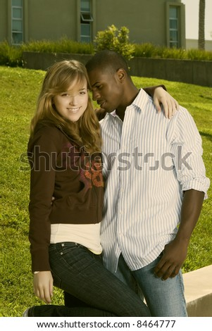 young interracial couple standing in the park - stock photo