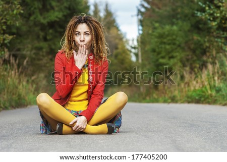 Young is surprised beautiful woman with dreadlocks in red clothes sits in lotus position on paved road. - stock photo