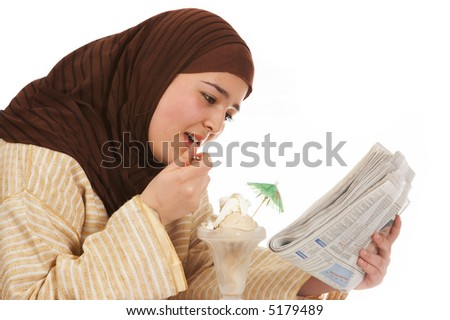 Young islamic woman reading her newspaper while enjoying an ice cream