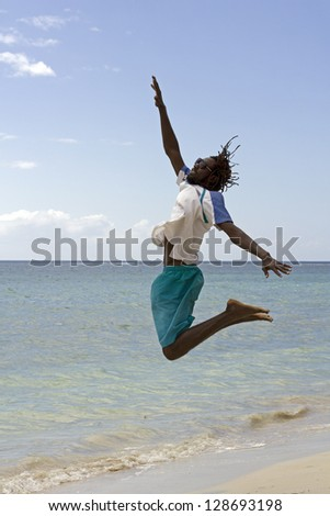young jamaican rasta jumping on the beach - stock photo