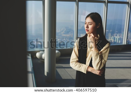 Young Japanese business woman is enjoying amazing city view outside the window, while is standing on the top floor of skyscraper office. Female entrepreneur is thinking about future project of company - stock photo