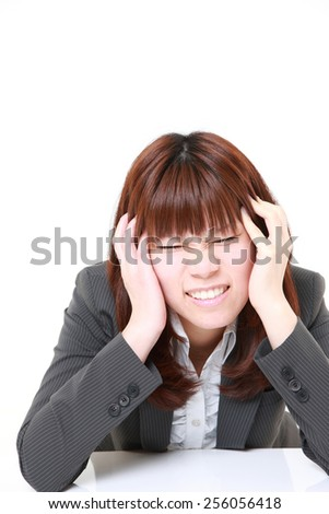 young Japanese businesswoman suffers from headache - stock photo
