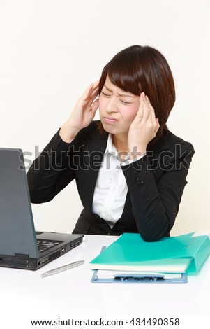 young Japanese businesswoman suffers from headache