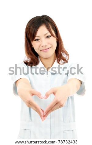 Young japanese female nurse shows fingers heart symbol