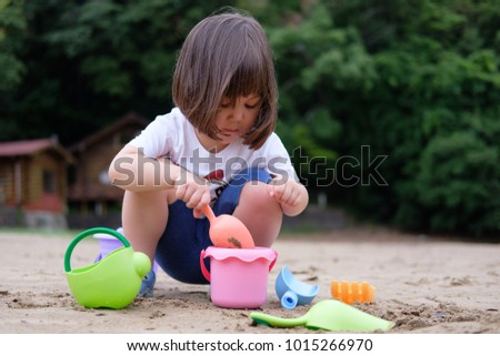 Young Japanese girl playing in the sand with her colorful toys.