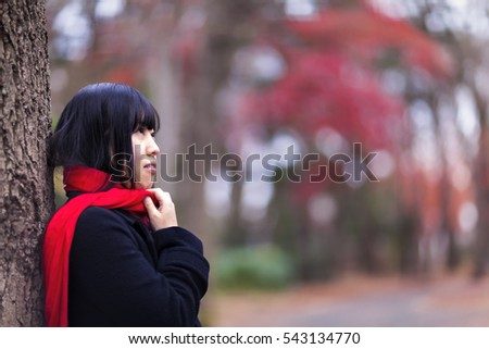 Young Japanese girl with a red muffler is standing in front of a tree during a cold weather.