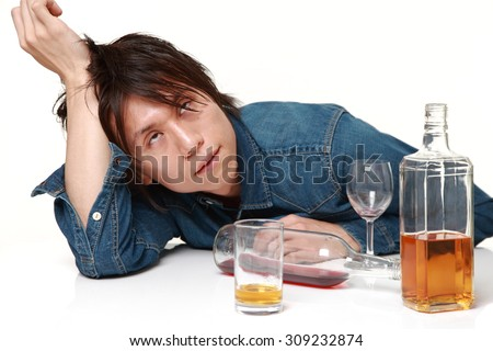 Young Japanese man in depression is drinking alcohol - stock photo
