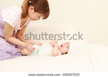 young Japanese mom changing her baby's diaper