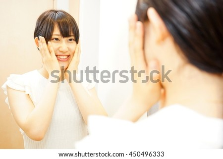 Young japanese woman caring her skin in a bathroom